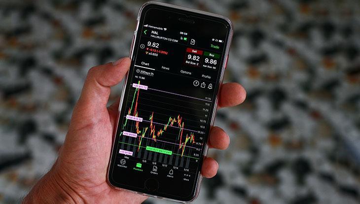 телефон в руках с открытой биржей акций